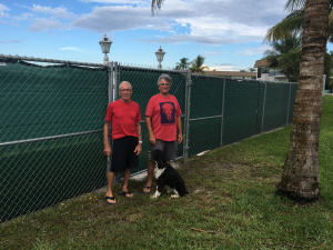 Tom Paquette and Tom Ryan, with his pet dog Jake, say the fence recently installed at Suni Sands blocks their views and prevents beach access. (Photo by Bill DiPaolo)