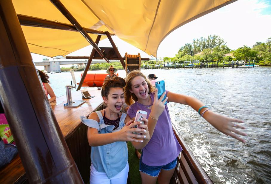 Giada Robinson,12, left, and Corinne McErlain,12, right, celebrate Lily Bucker's twelfth birthday on one of two Pontiki party pontoon boats on photo